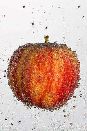 hostile: Fresh apple in a clear bubbly liquid on a white background.