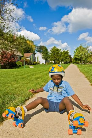 A young African American boy falls down while roller skating - wearing skates and a helmet. Stock Photo