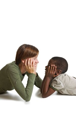 A young boy lying down staring face to face with a woman. Isolated on white.