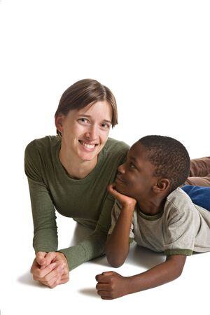 A young boy lying on front with a woman. Isolated on white.