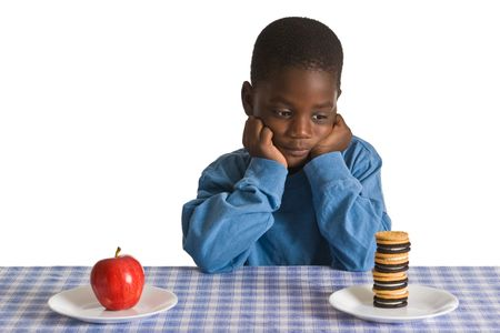 A young African-American boy with snacks - studio shot isolated on white.
