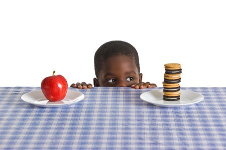 medical decisions: A young African-American boy gets ready for a snack - studio shot isolated on white.
