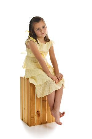 Little girl in a pretty yellow dress sitting on a wooden crate. One of series. Studio shot isolated on a white background.