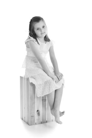 Little girl in a pretty dress sitting on a wooden crate. One of series. Black and white studio shot isolated on a white background. Stock Photo