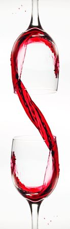 Two wine glasses and red wine creating an unusual dollar sign.