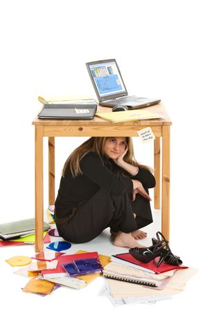 disorganized: Stressed and overworked business woman hiding under her desk to avoid dealing with too many tasks.  Isolated on white background.