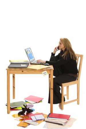 Young overworked business woman struggling to handle too many tasks with cell phone and laptop computer.  Isolated on white background. Stock Photo