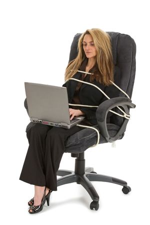 unfair: Beautiful young working on her laptop while tied to her office chair.  Isolated on white background.