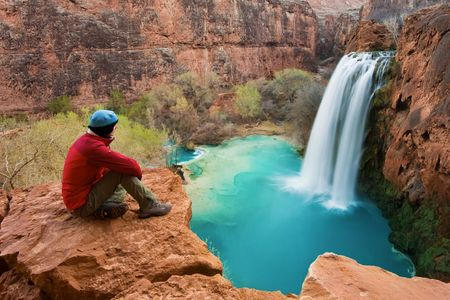 Woman sitting at the edge of a cliff watching Havasu Falls drop into its turquoise pool.