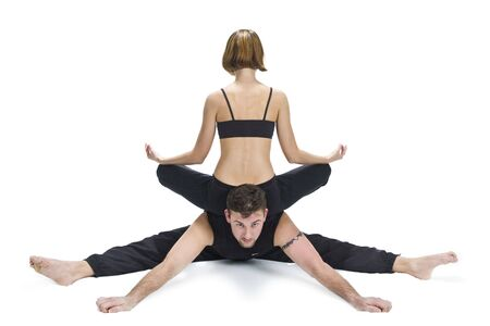 muscle toning: Male and female gymnasts practicing a complex double yoga pose.