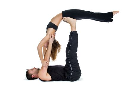 Male and female gymnasts practicing a complex double yoga pose.