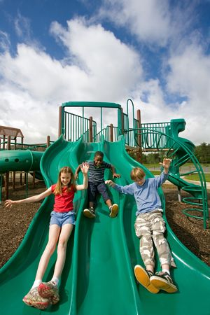 Three children playing on a green slide under a beautiful sky. A wide angle lens creates comic distortion of the foreground.