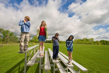 Four children standing on benches near a green field. Stok Fotoğraf