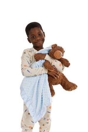 Young African American boy wearing pajamas and holding a blue blanket and a well-loved teddy bear. Isolated on a white background.