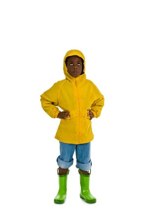 A young African American boy wearing a yellow rain slicker. Isolated on a white background. Stock Photo