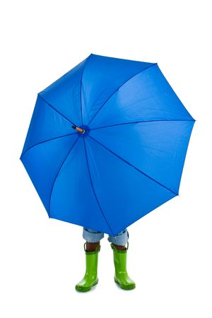 A young African American boy behind a big blue umbrella. Isolated on a white background. Stock Photo