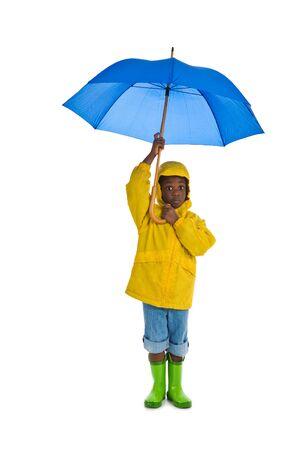 botas de lluvia: Un joven African American muchacho que llevaba una amarilla slicker la lluvia y con un paraguas azul. Aislada en un fondo blanco.