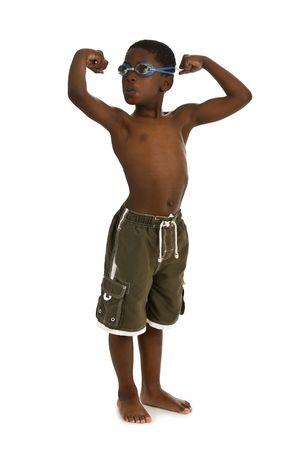 Een jonge African American jongen gekleed zwemmen schachten en bril, en de vertoning van zijn spieren. Geïsoleerd op een witte achtergrond.