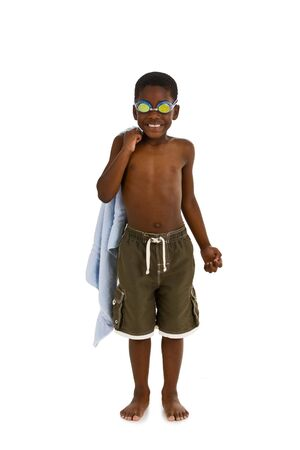A young African American boy wearing swim trunks and goggles, and carrying a towel. Isolated on a white background. Stock Photo
