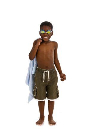 Een jonge African American jongen gekleed zwemmen schachten en bril, en met een handdoek. Geïsoleerd op een witte achtergrond.