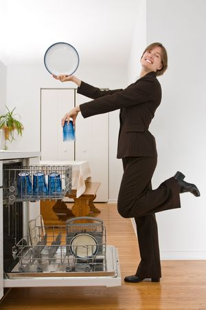 Young woman in a  suit loading the dishwasher in an exaggerated pose.