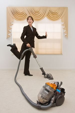 Young woman in a  suit vacuuming in an exaggerated pose. Selective focus on the vacuum.