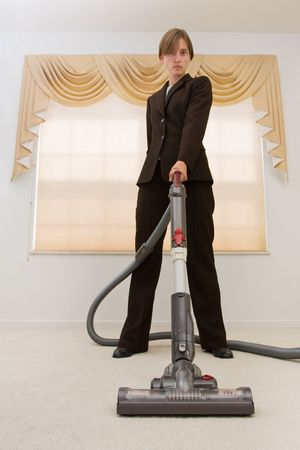 Young woman in a  suit vacuuming in an exaggerated pose. Selective focus on vacuum. Stock Photo