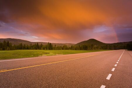 Beautiful sunset and rainbow over a road leading into distant mountains.