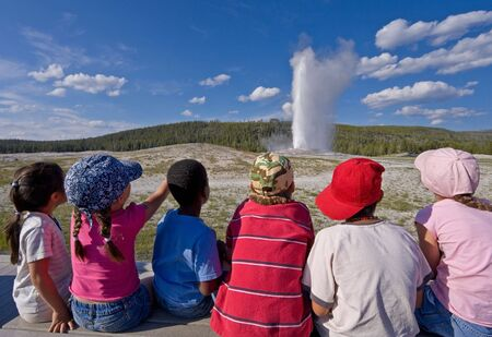 Six children of diverse backgrounds watching Old Faithful geyser erupt at Yellowstone National Park in Wyoming, USA.