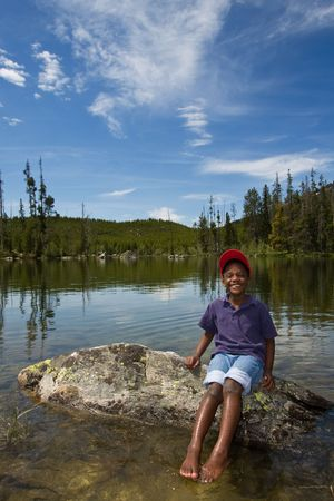 Young African American child playing in a lake at Yellowstone National Park in Wyoming, USA. photo