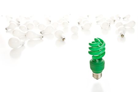 Bright green compact fluorescent light bulb in sharp focus with old incandescent bulbs littering the white background.