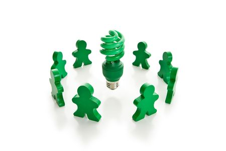 Circle of green wooden people surrounding a bright green compact fluorescent light bulb. Isolated on white.