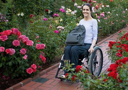 accessible: Beautiful young woman in a wheelchair visiting a rose garden in Oregon. Stock Photo