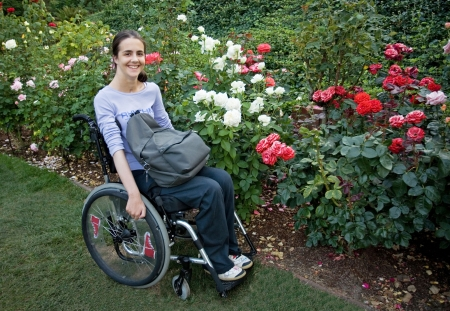 Beautiful young woman in a wheelchair visiting a rose garden in Oregon. Stockfoto