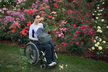Beautiful young woman in a wheelchair visiting a rose garden in Oregon. Stock Photo
