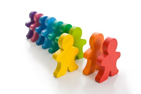 Line of colorful wooden people - one yellow person stand out of line. Isolated on a white background. Stock Photo