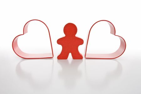 Red wooden person stands between red hearts. Isolated on white background.