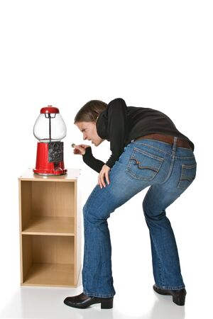 Confused or angry young woman in blue jeans tries to put a quarter into an empty gumball machine. photo