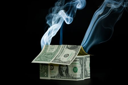 housing crisis: Little house made of money with smoke rising from it. Isolated on a black background.