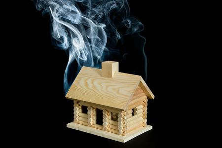 Log cabin with smoke rising from it. Isolated on a black background.