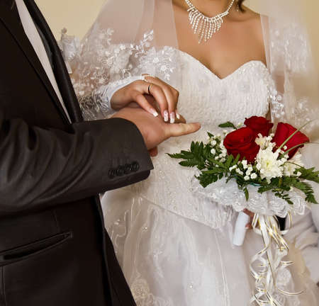 Closeup of bride putting a ring on groom s finger Stock Photo - 13300326