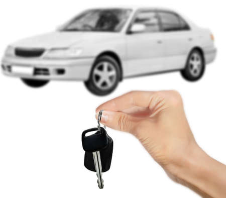 Hand with key and white car isolated on white