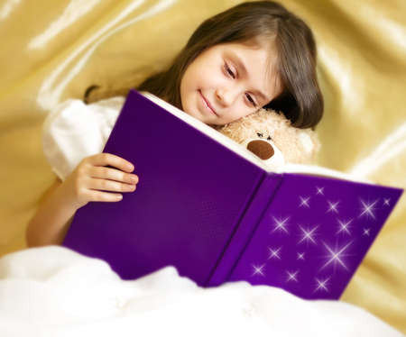 Adorable little girl reading book with her toy be Stock Photo