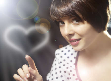 Beautiful woman drawing a heart in air Stock Photo