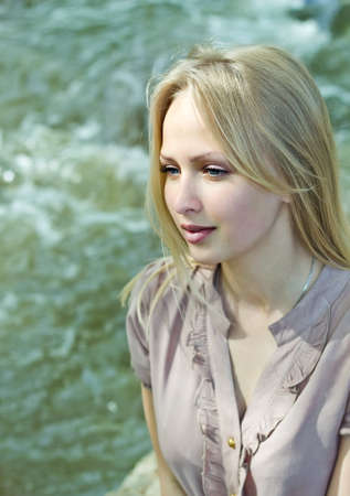 Beautiful blonde woman looking at river
