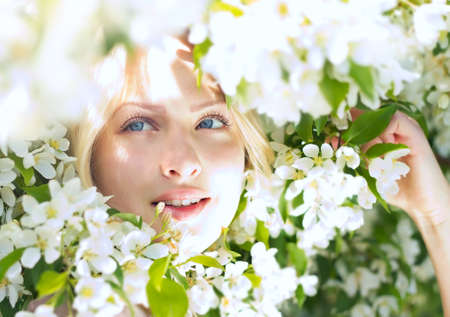 Closeup beautiful woman among blossom apple tree  Stock Photo