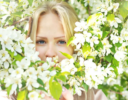 Closeup beautiful  woman face among blossom  tree branches