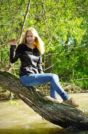 Young blonde woman sitting on dried-up tree
