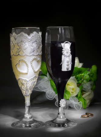Closeup glasses in bride and goom costumes in the darkness photo