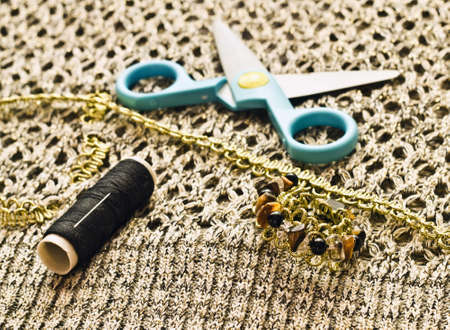 Closeup scissors, threads and beads on woolen thing